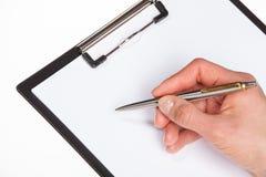 Руки женщины держа чистый лист бумаги в доске сзажимом для бумаги Стоковое Фото