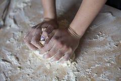 Руки женщины замешивая тесто на таблице стоковое фото