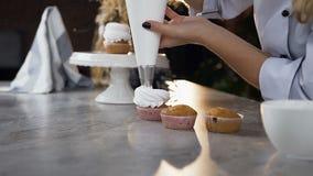 Руки женщины используя сумку печенья к установке сливк на торт акции видеоматериалы