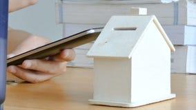 Руки женщины используя умный компьютер телефона и кладущ монетку денег в вычисление применения метафоры дома копилки передвижное  видеоматериал