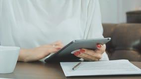 Руки женщины используя цифровую таблетку в кафе Стоковые Изображения RF