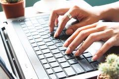 Руки женщины используя портативный компьютер, работая дома Стоковые Фотографии RF
