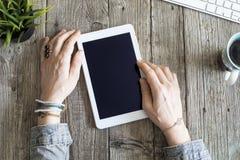 Руки женщины используя цифровую таблетку на деревянном столе Стоковые Фотографии RF