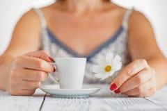 Руки женщины и кофе близких вверх с белым цветком Стоковая Фотография RF