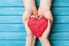 Руки женщины и человека держа красную форму сердца Предпосылка дня валентинки Святого Отношение, семья и концепция donorship стоковые фотографии rf