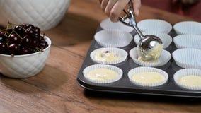 Руки женщины кладут тесто в голубые прессформы для пирожных акции видеоматериалы