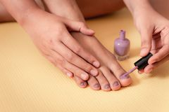 Руки женщины конца-вверх будучи покрашенным ее ноги ногтей стоковое фото rf