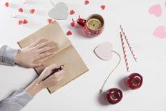 Руки женщины которая идет нарисовать карандашем в тетради На таблице чашка чаю с лимоном, яблоками и бумагой h Стоковые Изображения RF