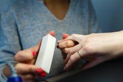 Руки женщины, который нужно делать в sel конца-вверх опиловки салона красоты ногтя стоковые изображения rf