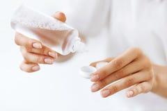 Руки женщины кладя жидкость от бутылки к коробке объектива стоковое изображение rf