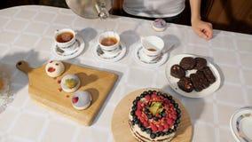 Руки женщины льют чай в чашках дома на таблице с помадками для того чтобы отпраздновать день рождения сток-видео