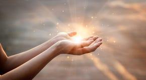Руки женщины моля для на предпосылки захода солнца стоковое изображение