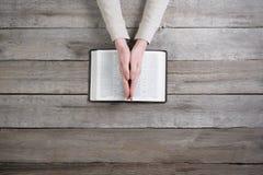 Руки женщины на библии она читающ и молящ Стоковая Фотография