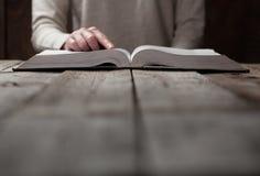 Руки женщины на библии она читающ и молящ Стоковая Фотография RF
