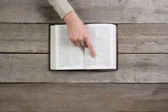 Руки женщины на библии она читающ и молящ Стоковое фото RF