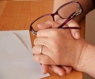 Руки женщины на стеклах владением таблицы Стоковое Фото