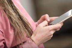 Руки женщины отправляя СМС на ее мобильном телефоне Стоковые Фотографии RF