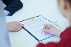 Руки женщины подписывая контракт Селективный фокус Стоковая Фотография RF