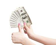 Руки женщины показывают большие пальцы руки вверх и выставки деньги Стоковая Фотография