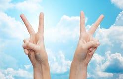 Руки женщины показывая победу или знак мира Стоковая Фотография RF