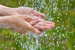 Руки женщины под дождем лета Стоковые Изображения