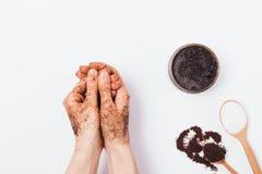 Руки женщины прикладывают косметику scrub земного кофе стоковые фото