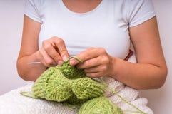 Руки женщины при иглы вязать с зелеными шерстями Стоковые Изображения
