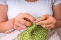 Руки женщины при иглы вязать с зелеными шерстями Стоковая Фотография