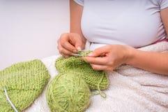 Руки женщины при иглы вязать с зелеными шерстями Стоковое фото RF