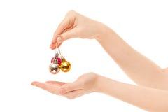 Руки женщины при изолированные игрушки Новый Год Стоковая Фотография