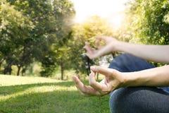 Руки женщины размышляя на йоге представляют на парке Стоковая Фотография