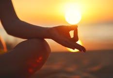 Руки женщины размышляя в йоге представляют на заходе солнца на пляже Стоковые Фото