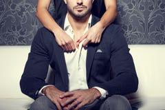 Руки женщины раздевают рубашку человека от позади стоковые изображения rf