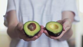 Руки женщины раскрывая и закрывая зрелый авокадо Закройте вверх с малой глубиной поля сток-видео