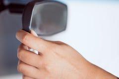 Руки женщины регулируя зеркало заднего вида в автомобиле Стоковая Фотография RF