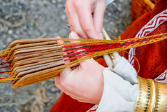 Руки женщины сплетя традиционный пояс Стоковое фото RF