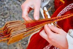 Руки женщины сплетя традиционный пояс Стоковые Изображения