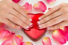Руки женщины с лаком для ногтей на коробке состава Стоковые Изображения RF