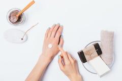 Руки женщины с голубым маникюром прикладывают косметическую сливк стоковое изображение rf