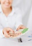 Руки женщины с деньгами наличных денег евро Стоковые Фотографии RF