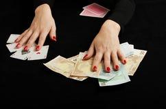 Руки женщины с играя карточками и деньгами стоковые фотографии rf