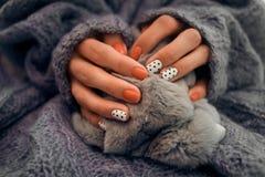 Руки женщины с красивым маникюром на предпосылке knit Тенденция fo Стоковое Фото
