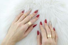 Руки женщины с красным искусством ногтя и ювелирные изделия на предпосылке меха стоковые изображения rf