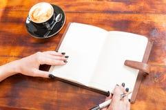 Руки женщины с открытой тетрадью снаружи с кофе Стоковое Изображение RF