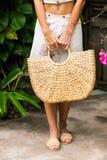 Руки женщины с сумкой соломы стоковое изображение