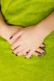 Руки женщины с темными ногтями на зеленом полотенце Стоковые Изображения RF