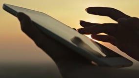 Руки женщины с цифровой таблеткой на заходе солнца сток-видео