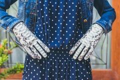 Руки женщины с черно-белыми модными перчатками питона snakeskin outdoors Стоковая Фотография RF