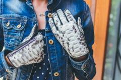 Руки женщины с черно-белыми модными перчатками питона snakeskin outdoors стоковые фото