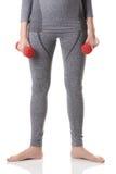 Руки женщины, тело, ноги с ногами отделились и повернулись к сторонам в нижнем белье спорт серого цвета термальном делая трениров Стоковая Фотография